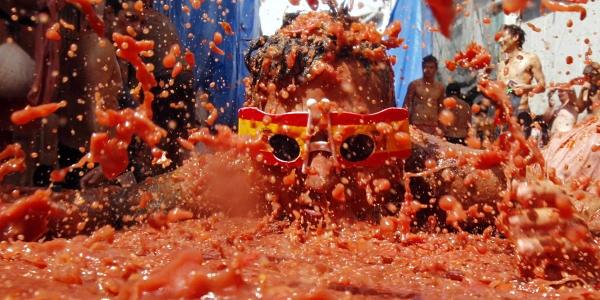 Un joven con gafas de los colores de España, disfruta de La Tomatina