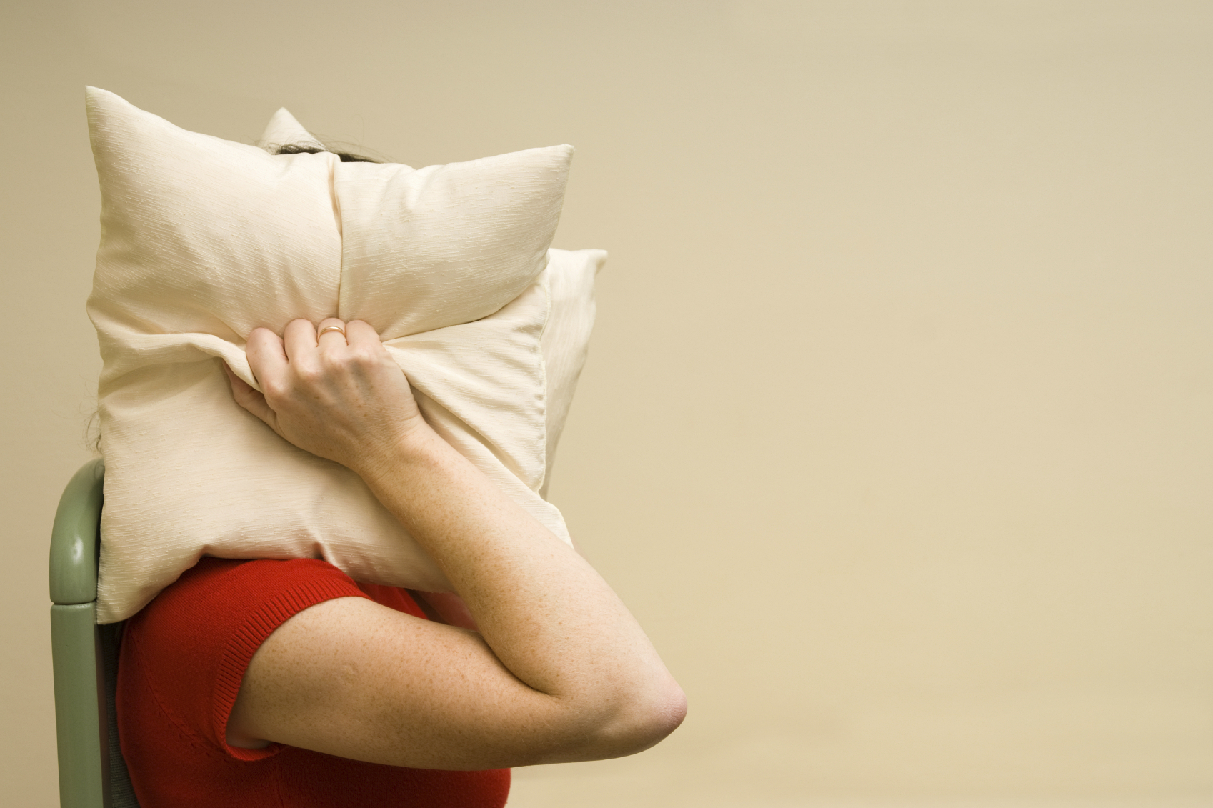 woman covering head with a pillow