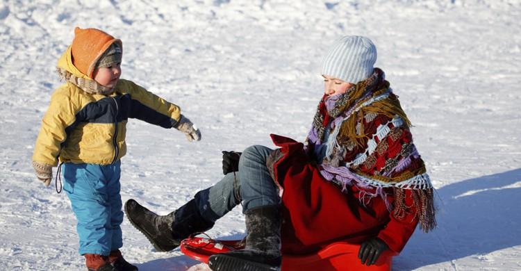 Familia divirtiendose en la nieve (iStock)