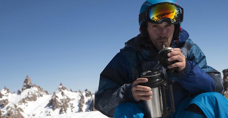 Un hombre toma una taza de mate en el medio de la nieve