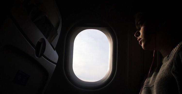 Una persona mira por la ventanilla del avión
