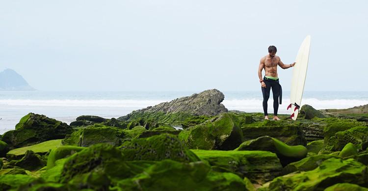 Un surfista en una pradera cerca de la playa