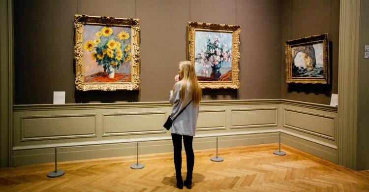 Una mujer admira un cuadro en un museo