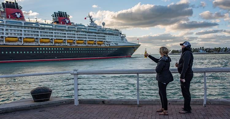 Dos personas saludan un crucero