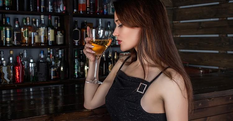 Una mujer bebe una copa de vino
